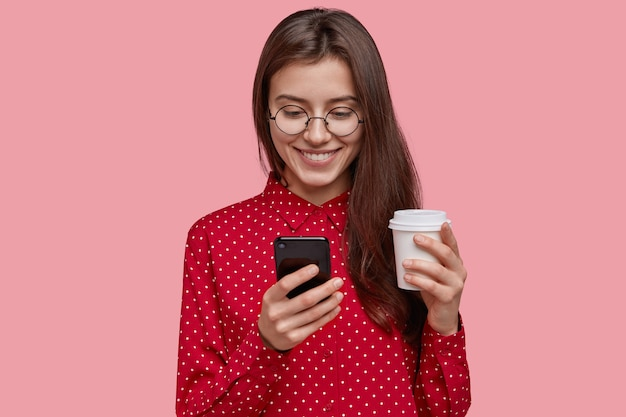 魅力的な喜んでいる若い女性は、ホットテイクアウトコーヒー、携帯電話を保持し、プレゼントとして新しいデバイスを受け取って喜んで、赤いシャツを着て、優しい笑顔を持っていた
