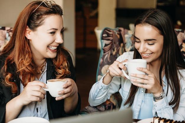 Очаровательные женщины больших размеров с рыжими волосами пьют кофе и улыбаются со своей прекрасной подругой в кафе.