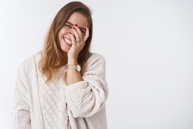 매력적인 긍정적인 귀여운 시시덕거리는 백인 성인 여자친구가 머리를 기울이고 얼굴을 찡그리며 손가락으로 엿보기를 하면서 웃으면서 얼굴을 붉히며 즐거운 즐거운 흰색 배경을 보고 있습니다.
