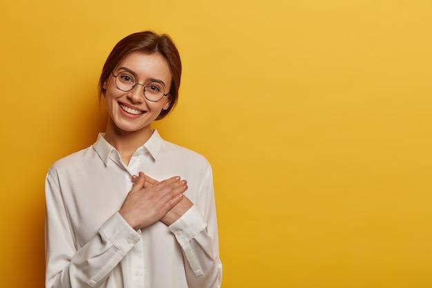 魅力的なポジティブなヨーロッパの女性は、手を胸に押し付け、贈り物に感謝の意を表し、助けに感謝し、丸いメガネと白いシャツを着ています