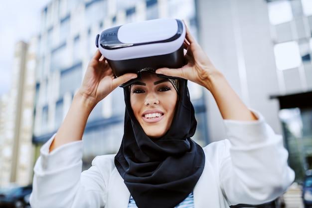 Очаровательная позитивная улыбающаяся стильная мусульманская женщина, стоящая на открытом воздухе и надевающая гарнитуру vr. тысячелетнее поколение.
