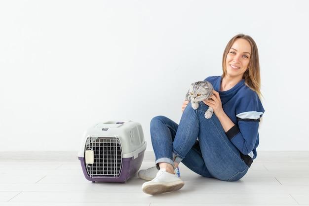 魅力的な前向きな若い女性は、床に座っている彼女の美しい灰色の折り畳みスコティッシュフォールドの猫を手に持っています