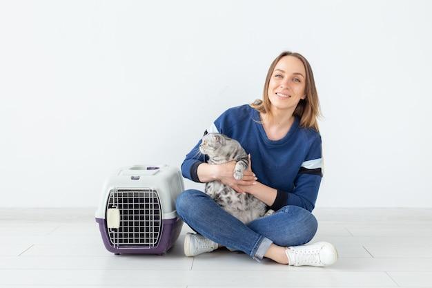 매력적인 긍정적 인 젊은 여자는 그녀의 손에 그녀의 아름 다운 회색 배 스코틀랜드 고양이에 앉아 보유