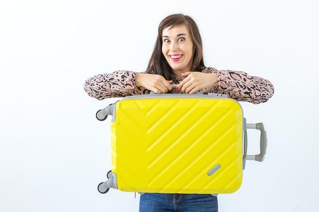 白い壁の表面に対して黄色のスーツケースに座ってポーズをとる魅力的なポジティブな若い女性。新しい発見の概念と旅行の利用可能性。コピースペース