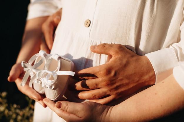 아기 신발 한 켤레와 함께 태양 빛에서 포즈를 취하는 동안 그녀의 남편에 의해 포용 된 매력적인 임산부