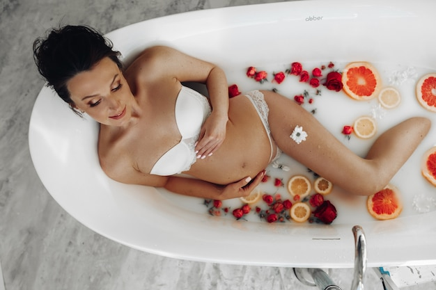 花とエッセンシャルオイルでリラックスした浴槽で冷やしながら笑顔の魅力的な妊婦