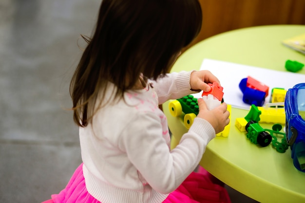 Charming preschooler playing with small constructor