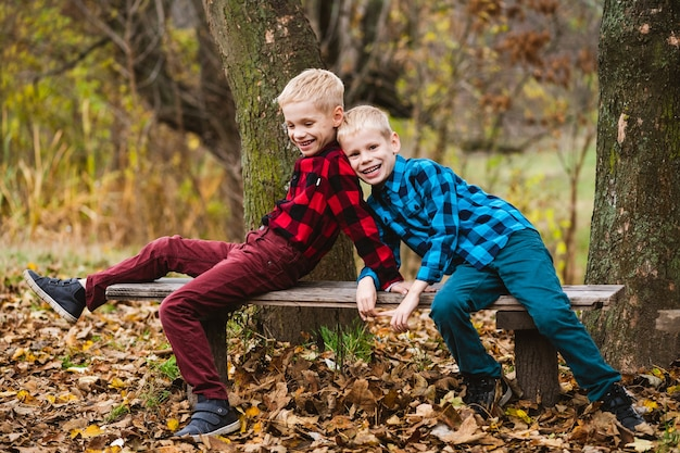 Charming preteen twin boys in checkered shirts smile and play together on romantic wooden bench in autumn park