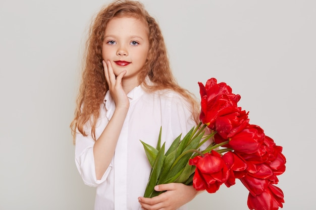 Charming pretty child girl wearing white clothing gets big bouquet of red tulips as present, looking at front wit confident expression