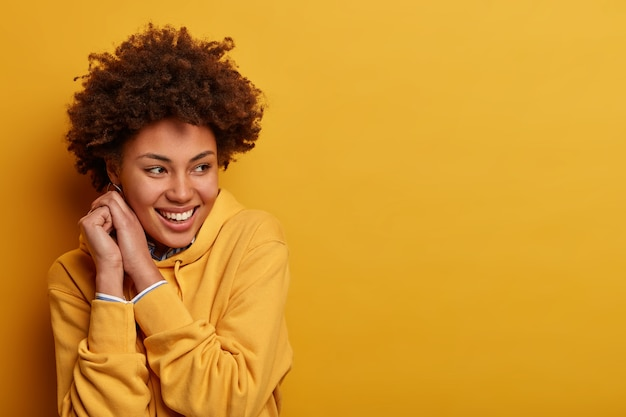 Charming pretty curly woman keeps hands near face, turns gaze aside, being in good mood, wears sweatshirt, poses over yellow wall, free space for your advertisement, has perfect beaming grin