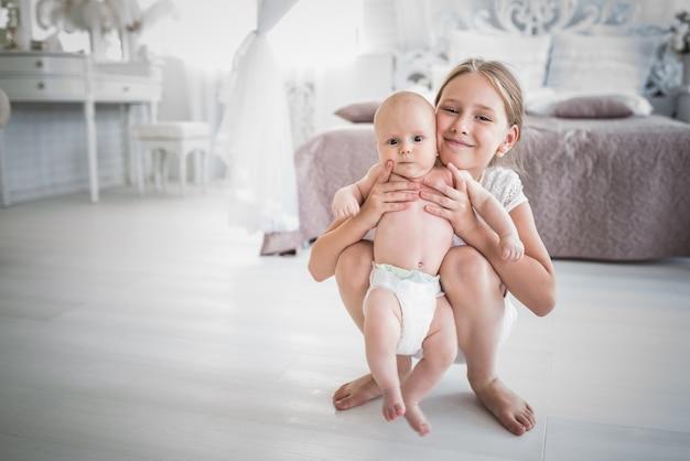 魅力的なかわいい女の子のティーンエイジャーは彼女の腕に彼女の弟を保持します