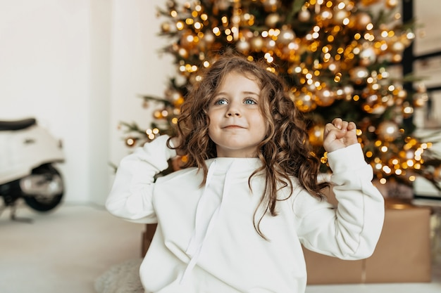 Charming pretty little girl with curls in white clothes smiling in front on christmas tree with lights