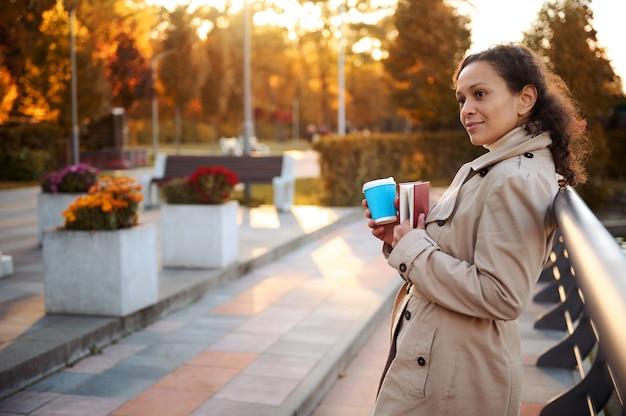 베이지색 코트를 입은 매력적인 미녀가 도시 공원에서 쉬고 있고, 난간에 기대어 서서 시선을 돌리고, 손에 든 하드백 책을 들고 아름다운 가을날 커피 휴식을 즐기고 있다