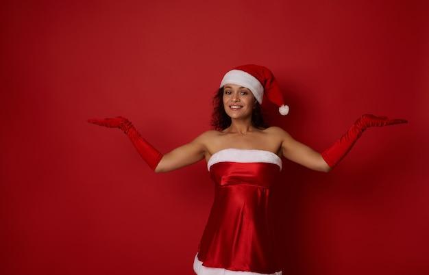 산타 카니발 의상을 입은 매력적인 여성은 아름다운 이빨 미소로 미소 짓고 손바닥에 복사 공간을 들고 카메라를 바라보는 빨간색 배경 위에 포즈를 취합니다. 메리 크리스마스, 새해