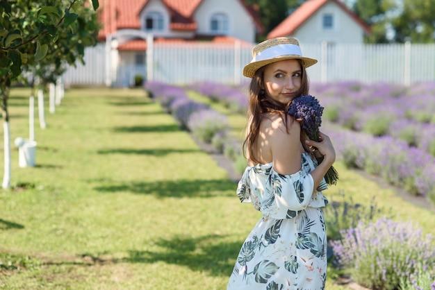 Очаровательная красивая женщина в соломенной шляпе с букетом лаванды в саду лаванды на заднем дворе.