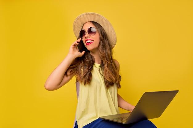 Affascinante bella donna che indossa occhiali e cappello estivo parlando al telefono e lavorando con il computer portatile
