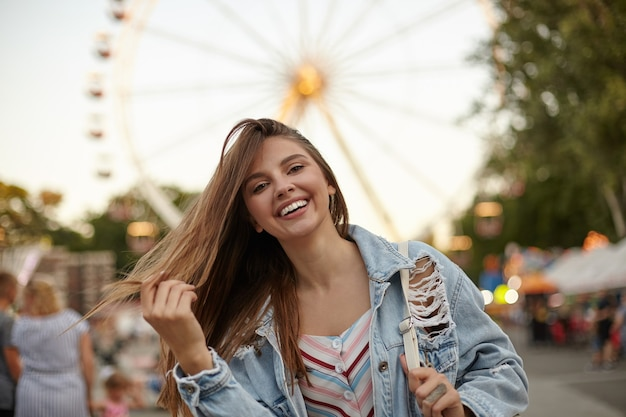カジュアルな服装で観覧車の上にポーズをとって、髪を振って、元気に笑って、前向きな感情の概念の長い茶色の髪を持つ魅力的なかわいい若い女性
