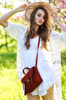 夏の帽子、咲く桜の背景に日当たりの良い庭を歩く白い光のドレスで長い髪の魅力的なかなり若い女性。リラクゼーション、カメラに微笑む、薄着、敏感、喜び