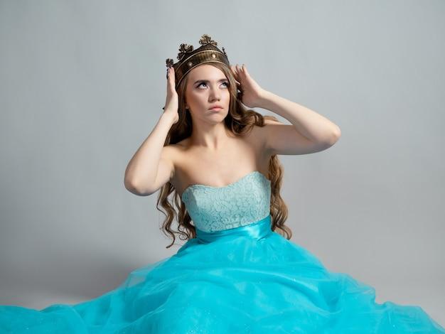 긴 물결 모양의 머리를 가진 젊은 아름다운 금발의 왕관을 쓴 매력적인 공주