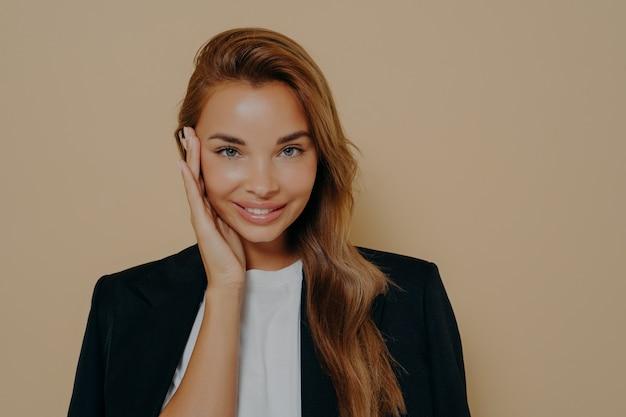 Очаровательная преуспевающая молодая бизнес-леди, одетая формально, нежно касаясь ее лица и улыбаясь в камеру после долгого рабочего дня, думает о чем-то приятном, позируя на бежевом фоне.