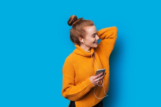 音楽を聴きながら、オレンジ色のセーターで青い背景にポーズをとっている間、彼女の髪に触れる魅力的な赤い髪の白人女性