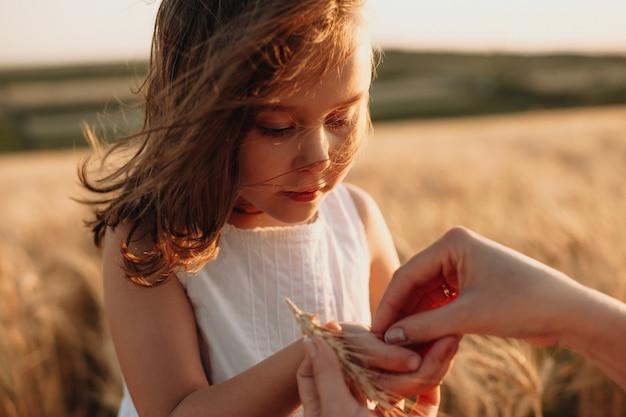 Очаровательная рыжая девушка с семенами пшеницы позирует в поле рядом с матерью