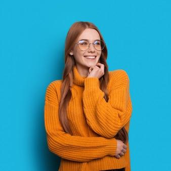 そばかすと黄色のニットのセーターを着た眼鏡を持つ魅力的な赤い髪の女性は、空きスペースのある青い壁にポーズをとっています