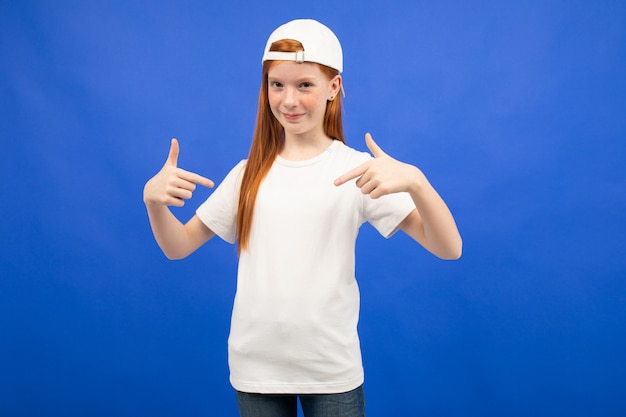Charming red-haired teenager girl in a white t-shirt with a print mockup blue