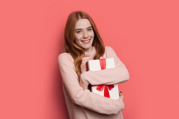 Очаровательная рыжая женщина с веснушками улыбается в камеру, обнимая подарок в теплом свитере, позирует на красной стене