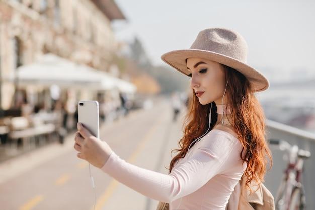 도시에서 산책하는 동안 셀카를 만드는 스마트 폰으로 매력적인 빨간 머리 여자