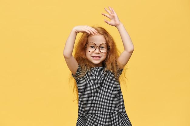 Очаровательная рыжая кавказская девочка в платье и круглых очках, эмоционально жестикулирующая, взволнованная позитивными хорошими новостями, с счастливой улыбкой