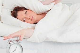 Charming redhaired woman waking up thanks to an alarm clock