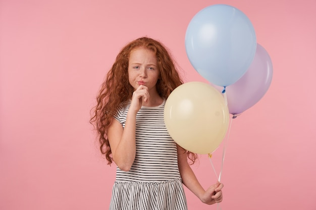 Charming redhead curly long haired girl in casual clothes standing over pink background, looking thoughtfully to camera and holding chin with raised hand, keeping air balloons in her hand
