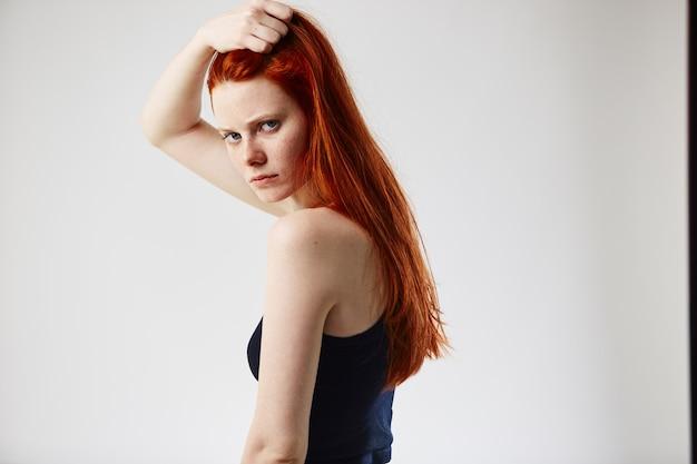 Очаровательная рыжая длинноволосая девушка в черном топе и джинсах держит руку на голове
