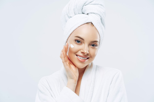Charming relaxed beauty woman applies face cream, cares about complexion, touches cheek with hand, smiles gently dressed in bath robe, wrapped towel on washed hair, isolated on white