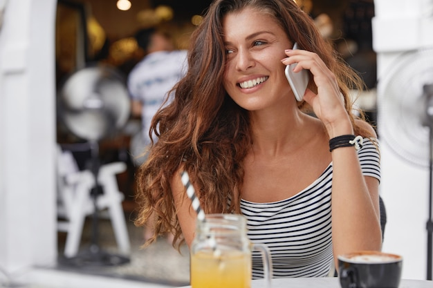 Charming relaxed female with positive smile sits at terrace cafe