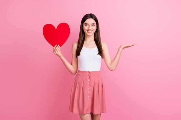 魅力的なロマンチックな女性は赤い紙のハートカードの手が空のスペースを示しています