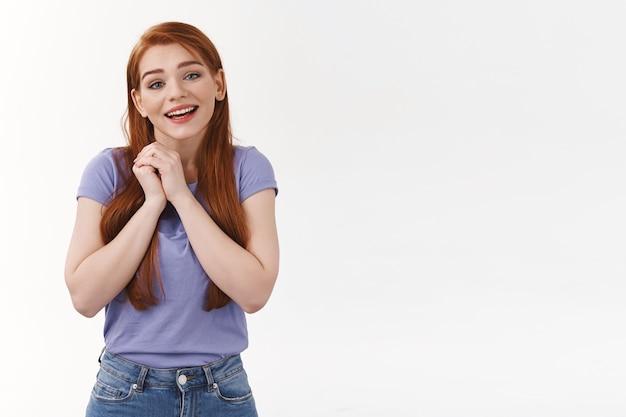 Affascinante donna romantica con lunghi capelli rossi, stringere le mani vicino al cuore e sospirare con ammirazione, adorare qualcosa di bello e carino, sorridente