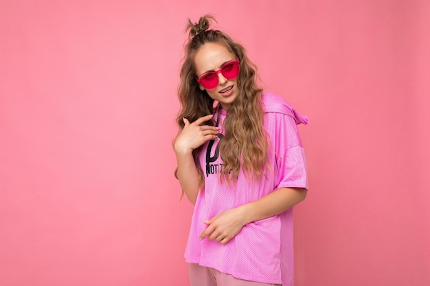 Очаровательная грустная молодая блондинка кудрявая женщина изолирована на стене розового фона, одетая в повседневную розовую футболку и стильные красочные солнцезащитные очки, глядя в камеру и спрашивая.