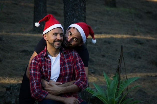 Charming scene of young homosexual couple with red christmas hats in forest park smiling men hug