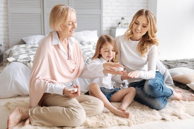 그녀의 손바닥에 크림 한 병을 가진 매력적인 수석 아가씨와 손녀가 크림을 가지고 어머니의 손에 크림을 바르십시오.