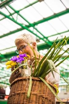 Charming senior woman buying flowers on market