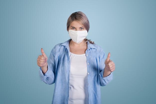 금발 머리와 파란색 스튜디오 벽에 같은 기호를 몸짓 얼굴에 의료 마스크와 매력적인 수석 여자