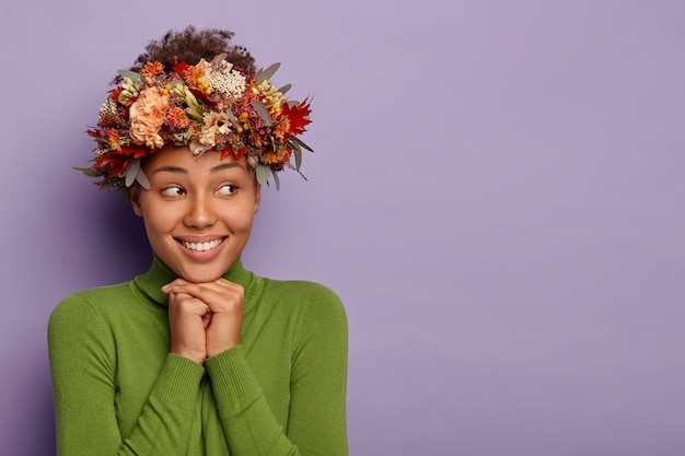 Charming sensual young woman with dark skin, smiles pleasantly, looks aside, wears seasonal wreath, green poloneck, isolated over purple background, copy space.