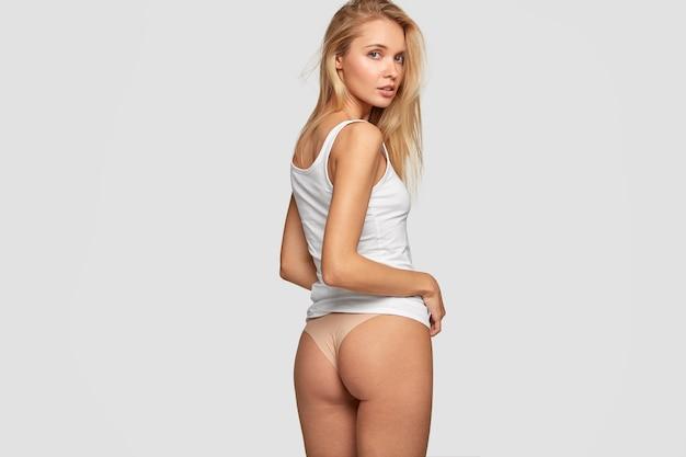 Affascinante modella sessuale in biancheria intima, indossa bikini, mostra i glutei, fa un passo indietro, essendo in buona forma fisica, modella contro il muro bianco.