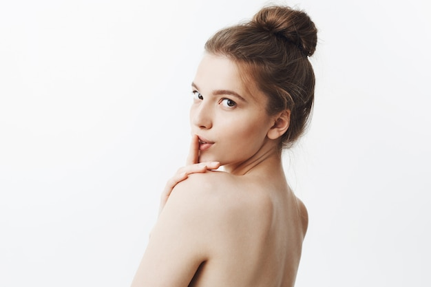 Charming sexy good-looking young caucasian woman with brown hair in fashionable hairstyle and naked body, holding finger in front of lips in three quoters