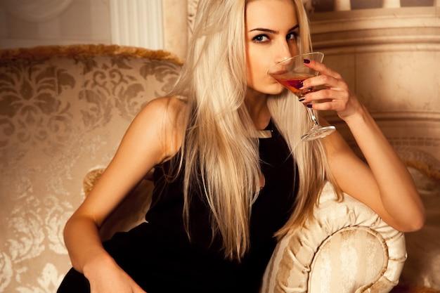 魅力的なセクシーな女性はマティーニを飲み、カメラを見て
