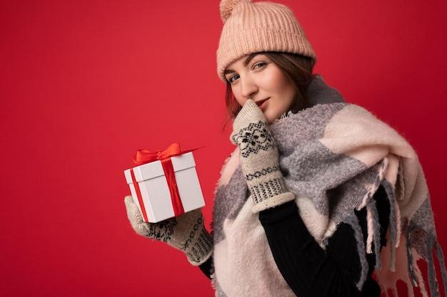 매력적인 섹시 긍정적 인 젊은 벽 여자는 겨울을 입고 붉은 벽 벽 위에 절연
