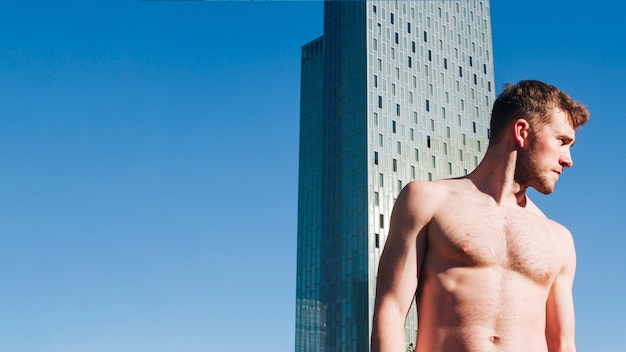 Charming shirtless man standing in front of modern building looking away