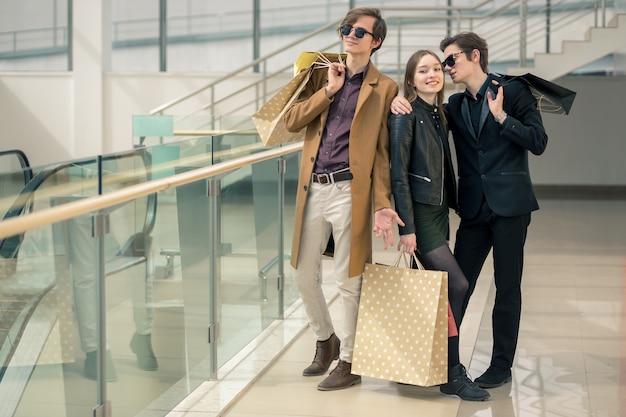 Очаровательные шопоголики с бумажными пакетами обсуждают что-то увиденное в торговом центре